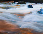 A long exposure softens the textures of Yosemite's powerful Merced River during springtime's high water. The pink tones are attributed to early morning light reflecting from the granite walls rising steeply above the river.