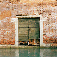 Boarded entrance door on a canal in Venice, Italy