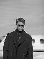 good looking man in a peacoat and sunglasses walking from a private jet in Santa Fe, New Mexico