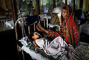An woman is seen taking care of her ill grandson at the pediatrics section of Maharani Laxmibai Medical College in Jhansi, Uttar Pradesh, India. The Indian government spends $1.4 billion a year - on programs that include weighing newborn babies, counseling mothers on healthy eating and supplementing meals, but none of this is yeilding results. According to UNICEF, some 48% of Indian children, or 61 million kids, remain malnourished, the clinical condition of being so undernourished that their physical and mental growth are stunted. Photo: Sanjit Das/Panos for The Wall Street Journal.Slug: IMALNUT