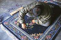 Man trimming carpets at the Tibetan Handicraft Center.