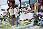 Two women in their 30s place flowers/say prayers for public official Miki Endo before a makeshift shrine in front of the battered remains of the Crisis Management Center in Minamisanriku, Miyagi Prefecture on 11 Sept. 2011, exactly 6 months after the March 11 disasters struck Japan. Endo is said to have saved thousands of lives in the area after she continued to shout warning calls to local people of the oncoming tsunami from the top of the building, sacrificing her own life in the process. The two women pictured -- who would not give their names -- were friends of Endo, who was just 25 when she was washed away by the waves. Photograph: Robert Gilhooly
