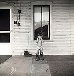 Toddler boy on back porch wearing fathers work boots.