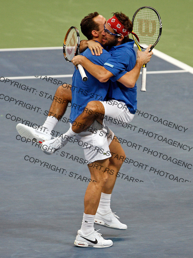 French Davis Cup players Michael Llodra (L) and Arnaud Clement (R) celebrate victory in their dubles match against Nenad Zimonjic and Viktor Troicki of Serbia. France leads 2:1 with only two matches remaining on Sunday. Davis Cup finals, Serbia vs France in Belgrade Arena in Belgrade, Serbia, Saturday, 4. December 2010. (credit & photo: Pedja Milosavljevic/SIPA PRESS)