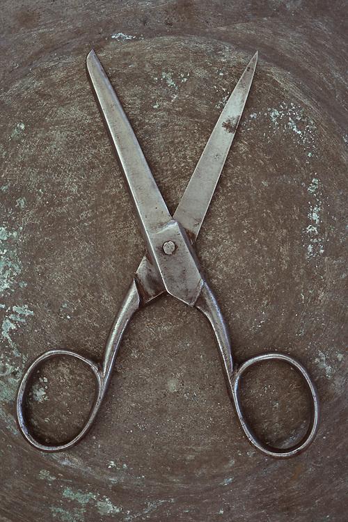 Vintage steel kitchen scissors lying wide open on tarnished metal