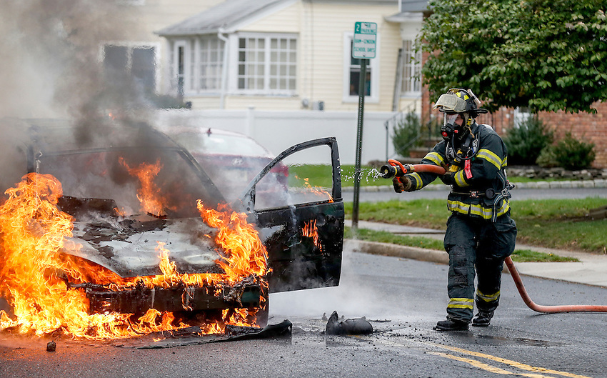 MANASQUAN, NJ — April 1, 2016 — Manasquan firefighter Kevin McCredie works on scene where a 2000 Ford Focus became fully engulfed in flames at about 9:40am on Broad Street, here.   photo by Andrew Mills