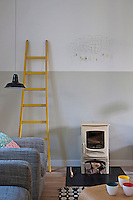 "A simple yellow-painted wooden ladder and a ""Cloud"" mobile by the artist Delphine Regneault are the only decoration in the living room"