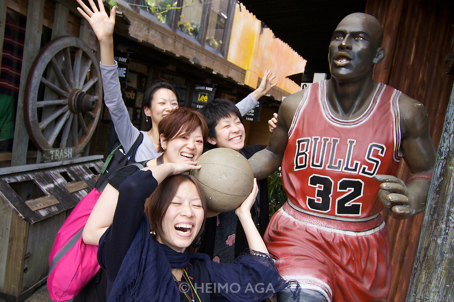 American Village. Japanese girls with Michael Jordan statue in Chicago Bulls outfit.