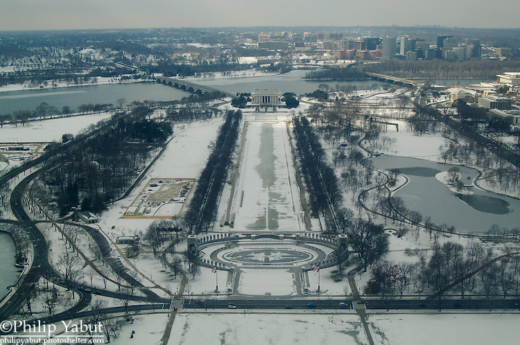 Looking west from the top of the Washington Monument, snow covers the Lincoln and World War II memorials and Constitution Gardens.