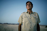 KUNENE, NAMIBIA - APRIL 25: Rudy Loutit, age 64, a park ranger, stands in a field on April 25, 2008 in Kunene, Namibia. Mr. Loutit did a 2-week survey with a walking safari with camels and a crew through 155 miles of proposed parkland through the savanna at Etosha National park, through rocky badlands, across the world's oldest desert, the Namib and the blinding dunes and fogy cliffs at Skeleton Coast on the Atlantic Ocean. Rudy has worked for over three decades to save the black rhinoceros from extinction through his organization, Save The Rhino Trust. The black rhino is now brought back from certain extinction and more than one hundred fifty of them roam this remote area. (Photo by Per-Anders Pettersson)..