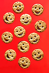 Smiling cookies filled with jam isolated on red background