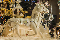 In another window of the Tincup Circle house, a white horse is harnessed to a sleigh.