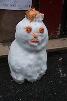 Snowman with carrot face and onion hat outside a Paris cafe.