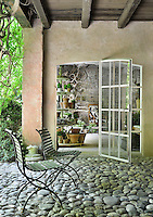 Two garden chairs are placed on a shaded terrace with a cobbled floor. An open glass door leads into a garden room beyond.