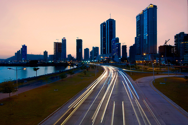 Dawn illuminajtes the high rises of Panama City and reduces speeding cars to streaks of light on Balboa Avenue and the Cinta Costera.