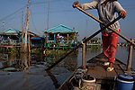 "Uyen, 49, a boat taxi operator, rows through a river neighborhood on the Hau Giang River, a tributary of the Mekong River, in Long Xuyen, the capital of An Giang Province, Vietnam. Uyen has operated a boat taxi for almost 20 years. When the Mekong River reaches Vietnam it splits into two smaller riveres. The ""Tien Giang"", which means ""upper river"" and the ""Hau Giang"", which means ""lower river"". Photo taken on Monday, December 8, 2009. Kevin German / Luceo Images"