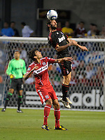 AC Milan defender Giuseppe Favalli heads the ball over Chicago Fire midfielder Baggio Husidic (9).  AC Milan defeated the Chicago Fire 1-0 at Toyota Park in Bridgeview, IL on May 30, 2010.