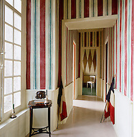 The walls of this corridor are painted in red, blue and white stripes complementing the pair of antique tricoleur flags propped against them