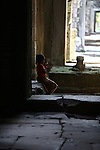 A little girl sits in an empty corridor at Preah Khan ruins in Angkor Thom, Cambodia. June 9, 2013.