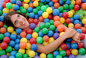 Teenage girl with physical disability lying in ball pool in residential respite care home.  MR