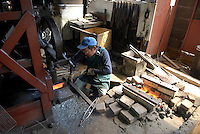 Working on a cooking knife at the Takahashi knife workshop. The machine pounds the knife flat.The company makes cooking knives for the shop in Tsukiji fish market..