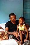 Kwame Mwakio and his daughter at home.  Kwame overseas scholarship programs in Likoni, Kenya for the Hatua Likoni Foundation