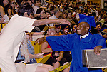 Photo by Phil Grout..Gregory McCord has just received his diploma.  He breaks from the line of classmates and runs to his grandmother, Verneither Manning, sitting in the audience who reaches out to her only grandson—now a a high school graduate.  McCord, a star runningback for Landsdowne, is going on to study sports medicine at Catonsville Community College.