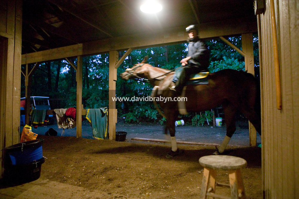 Jockey Julien Leparoux rides the track around a barn at the Biancone stable in Saratoga Springs, NY, United States, before an early morning practice ride, 4 August 2006.