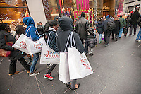 Shoppers with H&M shopping bags on Fifth Avenue in New York looking for bargains on Black Friday, the day after Thanksgiving, Friday, November 29, 2013. Many retailers, including Macy's, opened their doors on Thanksgiving or opened up for Black Friday the night before extending the shopping day into over 24 hours. (© Richard B. Levine)