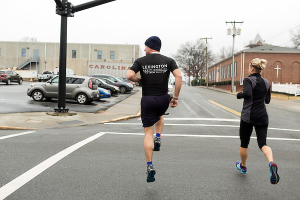 December 22, 2014. Lexington, North Carolina. <br />  Mayor Newell Clark jumps through an intersection as he heads out with his group for their workout.<br />   Newell Clark, the 43 year old mayor of Lexington, NC, leads a group of friends and colleagues on a 4 times a week exercise routine around downtown. The group uses existing infrastructure, such as an abandoned furniture factory, loading docks, stairs, and handrails to get fit and increase awareness of healthy lifestyles in a town more known for BBQ.<br /> Jeremy M. Lange for the Wall Street Journal<br /> Workout_Clark