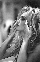 Photo of an Actress & Model Fixing her Hair. This is a Very grainy Black & White 35mm film scan.