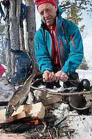 Saltoluokta Mountain Station, Jokkmokk, Lapland, Sweden, March 2013. After cleaning, the Arctic Char is hot smoked or grilled over the fire. Arctic survival training and winter bushcraft  in the frigid mountains of the Stora Sjofallet National Park and Sarek National Park with mountain guide Claes Jorgen Pohl.  Photo by Frits Meyst/Adventure4ever.com