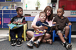 September 14, 2011. Raleigh, NC. . Susan Swearingen, the teaching assistant for the class, reads to (left to right) Delani Hamilton, Tyler Roth and Zaire Hines.. Project Enlightenment, a public pre-kindergarten program for at risk children, has been threatened with closure due to state wide budget cuts..