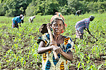 A woman pauses during her work in the fields at an agricultural school sponsored by the United Methodist Committee on Relief (UMCOR) in Kaminsamba, Democratic Republic of the Congo. Participants, some of whom stay at the center for several weeks, learn sustainable agricultural practices, animal traction, and beekeeping.