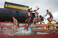 Womens 3000m Steeplechase pack jumps over the water hurdle at the Aviva London Grand Prix, Crystal Palace, London