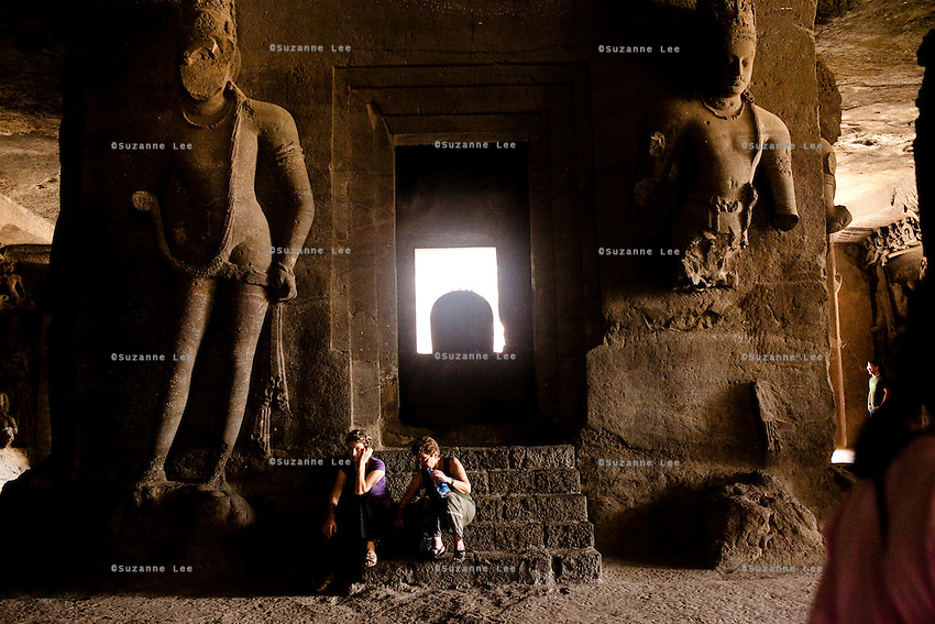 Tourists sit in front of the Shiva Lingam in the Elephanta Caves, a Hindu place of worship for the Lord Shiva, accessible by a long ferry ride in the Arabian sea, Mumbai, India. Photo by Suzanne Lee