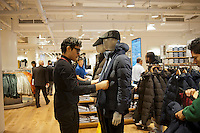 A floor supervisor adjusts a mannequin at the grand opening of the Uniqlo Flagship store on Fifth Avenue in New York on Friday, October 14, 2011.  The store is a staggering 89,000 square feet on multiple levels and is Fast Retailing's second store in the United States with a third opening next week in the Herald Square shopping district. The largest store on Fifth Avenue filled to the brim with affordable clothing it competes with stalwarts such as the Gap and Zara which are in the immediate proximity. Fast Retailing plans on opening 200 to 300 stores worldwide until 2020 and currently has 1000 stores. (© Richard B. Levine)