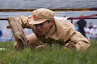 A competitor dressed in a PLA (People's Liberation Army) revolutionary era outfit crawls under 'barbed-wire' carrying a 'bomb' in the 'Bomb the Blockhouse' event at the Red Games. Held in Junan County, this sporting event is a nostalgic tribute to the communist era.