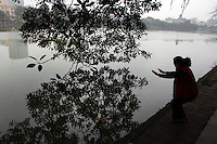 An elderly lady exercise on a misty morning beside Hoan Kiem Lake, Hanoi, Vietnam.. For a county not know for it's sporting prowess, Hanoi, Vietnam's capital, appears to be gripped in a fitness frenzy. Before 6am street corners, parks and lake sides are a hive of activity as keep fit classes, Tai chi and personal exercise regimes are seen in abundance around the city. Particularly noticeable are Women's keep fit classes, often accompanied by loud poor quality western disco beat music as the occupants of the city get fit come rain or shine. Hanoi, Vietnam. 18th March 2012. Photo Tim Clayton
