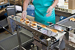 A member of staff loads packaged sasa-kamaboko onto a conveyor belt to be packaged at Oizen Shoten's factory in Tome City, Miyagi Prefecture, Japan on 11 Sept. 2012.  Photographer: Robert Gilhooly