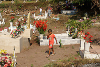 Girl walking through the town cemetery, El Quelite near  Mazatlan, Sinaloa, Mexico