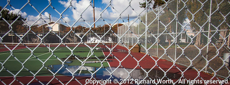 Pools of rain water on a tennis court reflect fluffy clouds behind a lattice of steel diamonds - a chain link fence.