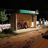 DOBRZYKOW, POLAND, MAY 23, 2010:.Rescue workers eating in  a bus stop, by the sand bags wall, late at night..The latest chapter of disastrous floods in Poland has been opened today, May 23, 2010, after Vistula river broke its banks and flooded over 25 villages causing evacualtion of most inhabitants..Photo by Piotr Malecki / Napo Images..DOBRZYKOW, POLSKA, 23/05/2010:.Strazacy pozna noca jedza posilek siedzac na porzystankuy autobusowym obok sciany z workow z piaskiem. Najnowszy akt straszliwych tegorocznych powodzi zostal rozpoczety dzis gdy Wisla przerwala waly na wysokosci wsi Swiniary kolo Plocka..Fot: Piotr Malecki / Napo Images ..