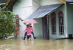Two people leave a flooded house during November 2014 flooding in Meulaboh in Indonesia's Aceh province. Flooding in the region has grown worse because of climate change and the proliferation of palm oil plantations.