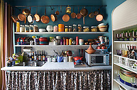 In the kitchen jars, crockery and glassware are ranged on open kitchen shelves built from marble above a matching marble work surface with a stainless-steel sink