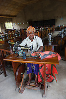 Africa, DRC, Democratic Republic of the Congo, Goma, Lake Kivu, Global Fund for Women project. PAIF organization safe house shelter for women in Mugunga. The land was bought with GFW grant. Tumaini Gentile, (20 years). I was 15 years old and out collecting firewood when a DRC government soldier raped me. Now that child is four years old. Two years ago someone else abused me and that resulted in another baby. Here I'm learning sewing and, it's good way to support myself as well as watch my children. I received a sewing machine from the GFW grant to work on at home and will buy the locally made base for $30. I can make 4 uniforms in two days and earn $3-5 each. Even my brothers are learning from me.