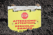 Warning sign buried in ash and lapilli, Mount Etna Volcano, Sicily, Italy.