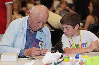 New York, NY, USA - June 23, 2012: John Lapko, NJ, teaches a young member how to fold a special model before classes begin. The OrigamiUSA 2012 Convention held at Fashion Institute of Technology, New York, attracts members from the USA with visitors from Asia, the Americas, and Europe. Attendees exhibit their work and take part in classes, and an exhibition of big folding.