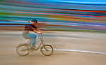 A rainbow cyclist races through traffic on Mong Kok streets, in Hong Kong.