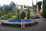 "Portmeirion, in North Wales, is a resort, where no one has ever lived. A self-taught Welsh architect named Sir Clough Williams-Ellis built it out of architectural salvage between the 1920s and 1970s, loosely based on his memories of trips to Portofino. Including a pagoda-shaped Chinoiserie gazebo, some Gothic obelisks, eucalyptus groves, a crenellated castle, a Mediterranean bell tower, a Jacobean town hall, and an Art Deco cylindrical watchtower. He kept improving Portmeirion until his death in 1978, age 94. It faces an estuary where at low tide one can walk across the sands and look out to sea. At high tide, the sea is lapping onto the shores. Every building in the village is either a shop, restaurant, hotel or self-catering accomodation. The village is booked out at high season, with numerous wedding receptions at the weekends. Very popular amongst the English and Welsh holidaymakers. Many who return to the same abode season after season. Hundreds of tourists visit every day, walking around the ornamental gardens, cobblestone paths, and shopping, eating ice-creams, or walking along the woodland and coastal paths, amongst a colourful assortment of hydrangea, rhododendrons, tree ferns and redwoods. The resort boasts two high class hotels, a la carte menus, a swimming pool, a lifesize concrete boat, topiary, pools and wishing wells. The creator describes the resort as ""a home for fallen buildings,"" and its ragged skyline and playful narrow passageways which were meant to provide ""more fun for more people."" It does just that.///A child wishing a wish in the wishing well. Ornamental central gardens of Portmeirion village. Flanked by Dome Gallery, Gothic tower, Renaissance collonades, with lwans, flowerbeds, topiary, pools and fountains."